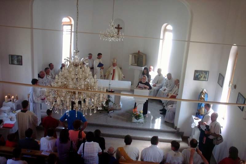 Biskup u pratnji služitelja prolazi kroz crkvu i škropi blagoslovljenom vodom